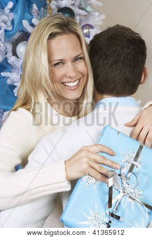 Portrait of a happy female with gift box embracing man and Christmas tree in the background