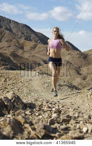 Full length of a beautiful Caucasian woman jogging in mountains