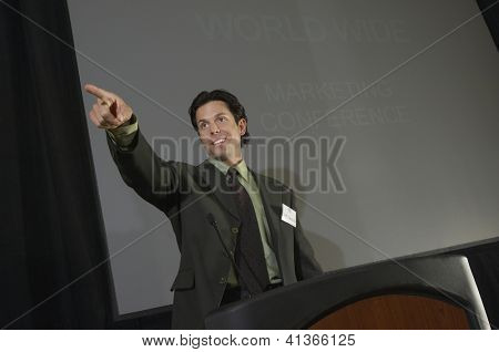 Businessman pointing while giving a lecture at podium