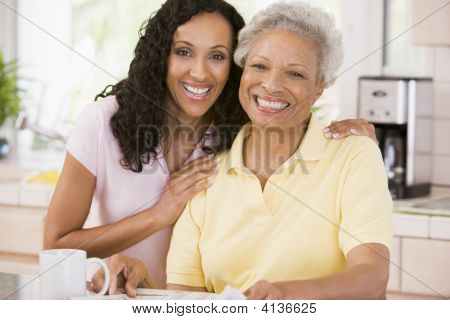 Two Women In Kitchen With Newspaper And Coffee Smiling