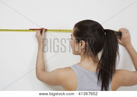 Rear view of a young woman making a mark on white wall with measure tape