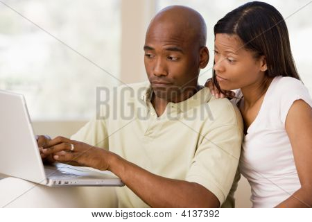 Couples In Living Room Using Laptop