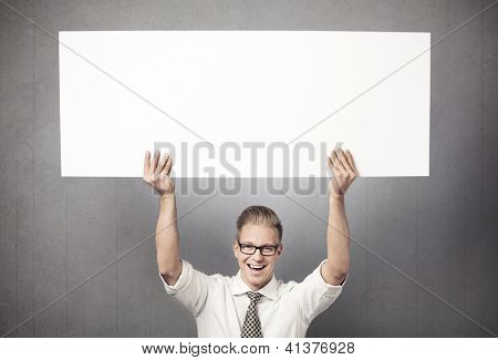Happy handsome businessman holding white blank horizontal billboard with space for text isolated on grey background.