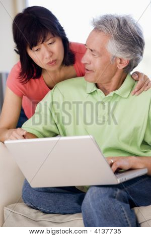Couples In Living Room With Laptop Smiling
