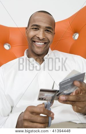 Portrait of an African American man cutting credit cards
