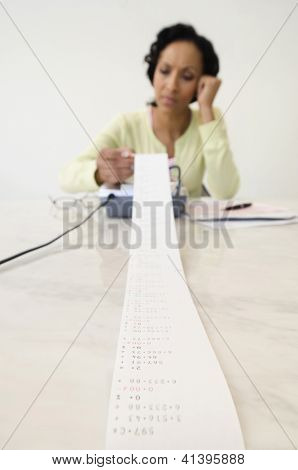 Tensed African American woman working on huge finances at home