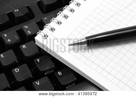 Notepad with pen on a black computer keyboard