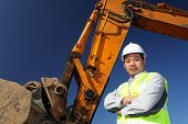 pic of heavy equipment operator  - portrait operator of excavator standing on location site - JPG