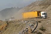 garbage trucks arriving at a landfill site
