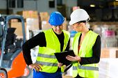 stock photo of forklift  - Worker or warehouseman and his coworker with clipboard at warehouse of freight forwarding company - JPG