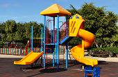 stock photo of playground  - Playground surrounded by trees on a sunny day - JPG