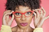Portrait of an African American woman wearing retro style glasses over colored background