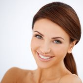 Head and shoulders studio portrait of a smiling happy beautiful woman with a lovely fresh natural co