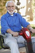 stock photo of scooter  - Portrait of a cheerful senior man on electric scooter - JPG