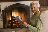 picture of current affairs  - Man sat in front of an open fire holding a newspaper - JPG