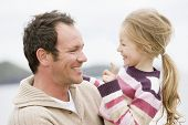 stock photo of father daughter  - Portrait of man and daughter on beach in wintertime - JPG