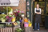 stock photo of flower shop  - Woman florist stoof outside shop - JPG
