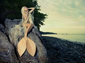 picture of mermaid  - Beautiful fashionable mermaid sitting on a rock by the sea - JPG