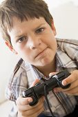Young Boy Holding Video Game Controller Looking Confused poster