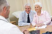 foto of elderly couple  - Senior man having consultation with male gp - JPG