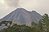 stock photo of belching  - The Arenal Volcano belching smoke into the sunset - JPG