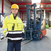 Man, waring safety clothes, including a hard hat, standing proudly in front of his forklift truck in