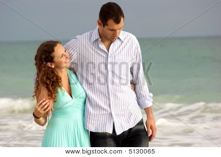 Couple Walking Along The Seaside  With Their Arms Around Each Other