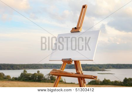 A Blank Canvas Rests On A Easel On Lake Landscape