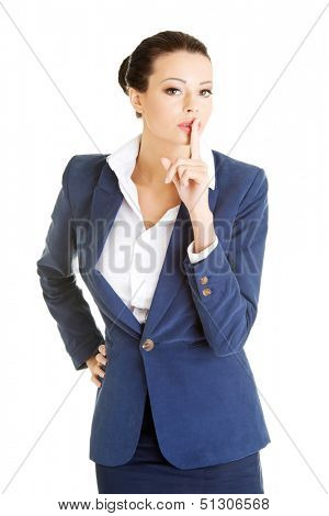 Portrait of attractive business woman with finger on lips, gesturing for quiet