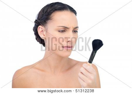 Serious natural model holding and looking at her powder brush on white background