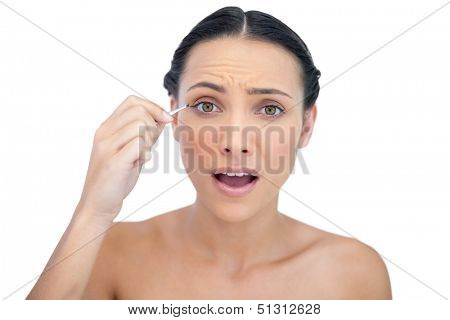 Astonished natural model using tweezers on white background