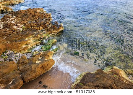 Seabed Seen Through Clear Waves Crashing Stones On Shore