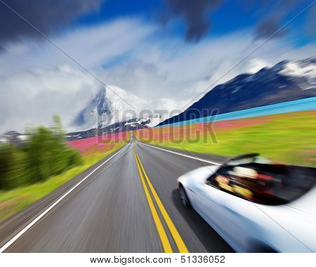 Mountain landscape with road and sports car in motion blur