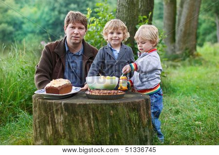 Young Father And Two Little Boys Picnicking In Nature Forest Near Lake