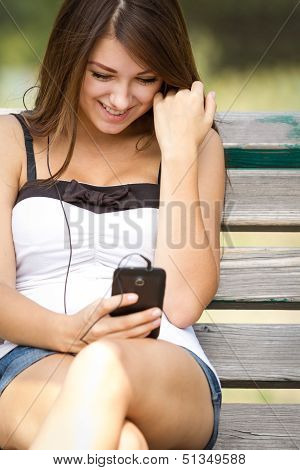 Happy Teen Girl Listening To Music On Smartphone