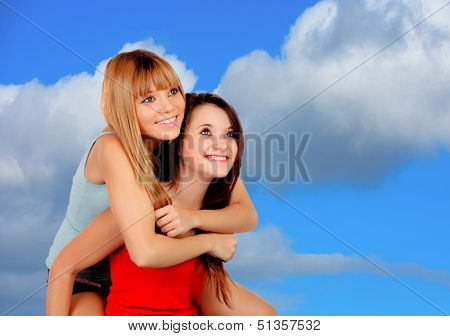 Two beautiful girlfriends on the outside with a beautiful blue sky background