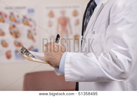 A Left Handed Doctor Writes On A Patients Chart.