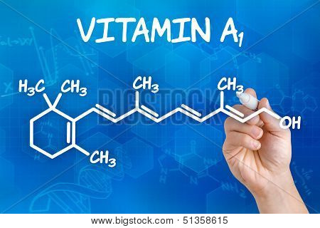 Hand with pen drawing the chemical formula of Vitamin A