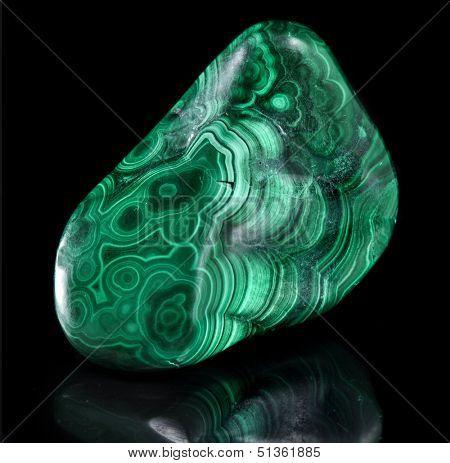 Polished malachite stone close up  with reflection on black background