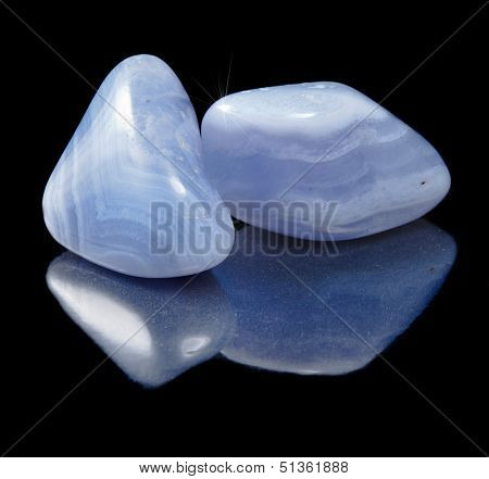 Two Blue Agate (sapphirine) stone close up  with reflection on black background