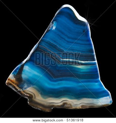 A slice of blue agate crystal with reflection on black surface background