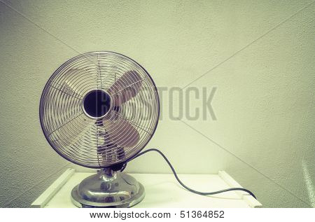 Old steel fan, grunge wall on background, vintage 1950s style