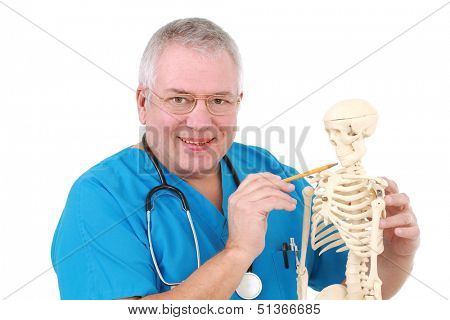 Man dressed in medical uniform inspects a replica of a human skeleton.