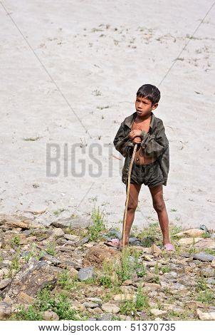 KALANKI, NEPAL - APRIL 2: Portrait of unidentified Nepalese herder boy with a rod on April 2, 2009 in Kalanki Village, Kathmandu, Central Region, Nepal.