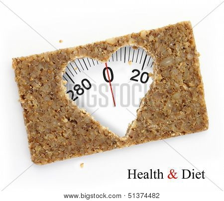 Multigrain slice of bread as weighing scale, in shape of heart, isolated on white