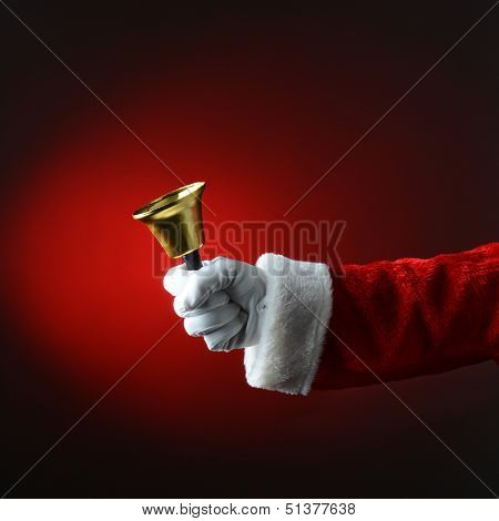 Santa Claus ringing a bell with a red background. Square Format with only Santa's hand and arm visible.