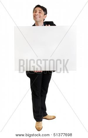 Businessman or salesman in a smart suit standing with a toothy ingratiating grin holding a blank sign in his hands with copyspace for your text or advertisement