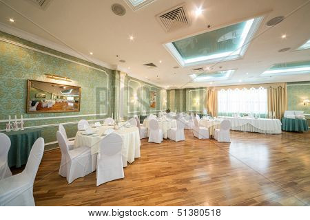Beautiful room with elegant tables in a restaurant decorated for a wedding celebration