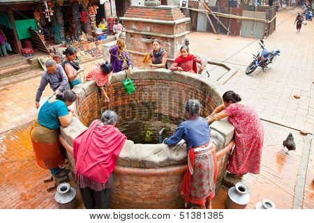 KATHMANDU,NEPAL-MAY 20: Nepalis drinking water extracted from wells on May 20, 2013, Lalitpur city, Nepal. Supply of drinking water is a big problem in Kathmandu valey.