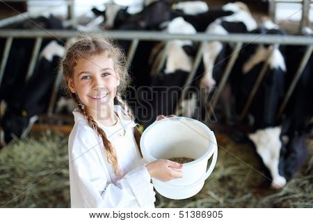 Little beautiful girl holds white bucket with food and smiles in stall with many cows.